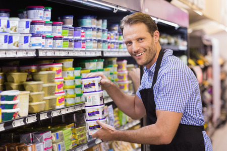 food shelf: Portraits of a smiling handsome holding a dairy products in supermarket