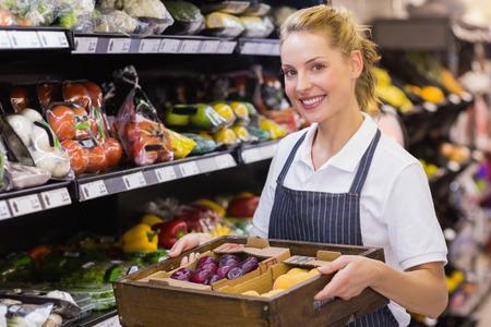 rubia: Retrato de un trabajador rubia sonriente sosteniendo una caja con verduras en supermarker
