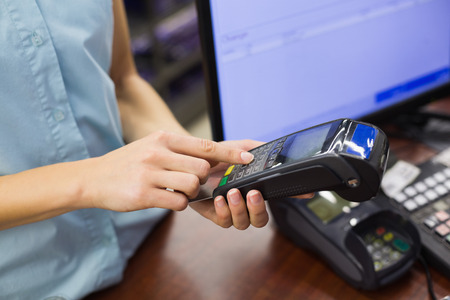 cash register: Woman at cash register paying with credit card in supermarket