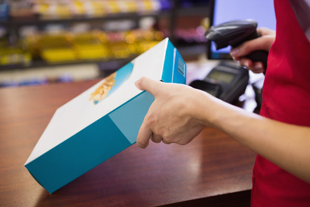 cereal box: Female worker scanning cereal box at supermarket