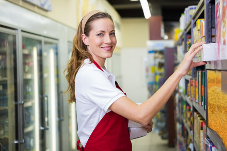 grocery store: Happy pretty woman putting product on shelf at supermarket Stock Photo