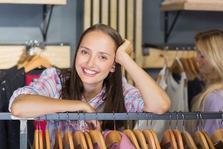 Hübscher Brunette mit Kopf auf der Hand lächelnd in die Kamera im Kleidungspeicher Standard-Bild
