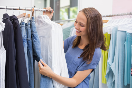 clothes rack: Enthusiastic pretty brunette browsing in the clothes rack