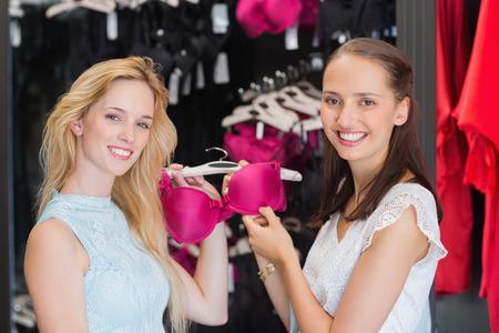 pink bra: Happy women showing a bra in shopping mall