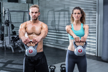 Portrait of a muscular couple lifting kettlebells Stock Photo