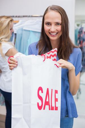 discounted: Portrait of a pretty brunette opening a discounted bag Stock Photo