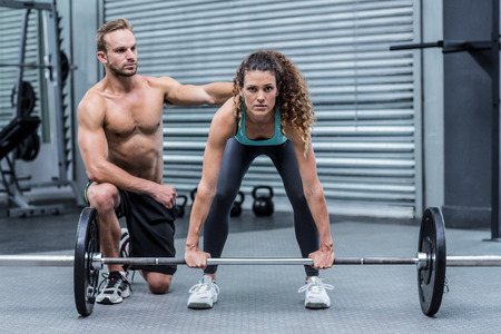 crossfit: Attentive muscular woman lifting weight with her trainer behind