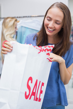 discounted: Happy pretty brunette opening a discounted bag Stock Photo