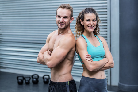giving back: Muscular couple giving back to back with crossed arms
