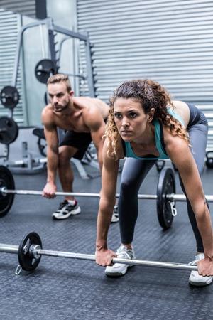 levantar pesas: Vista lateral de una pareja a punto de musculoso levantar pesas