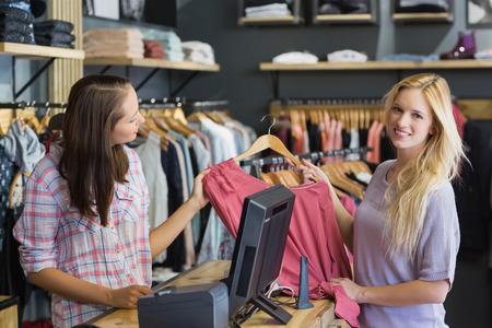 tienda zapatos: Sonriente rubia haciendo compras y mirando a la cámara en la tienda de ropa
