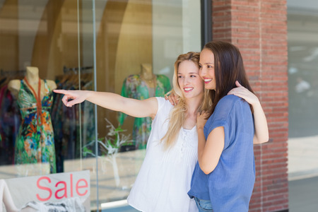 arms around: Smiling girl friends with arms around pointing away Stock Photo