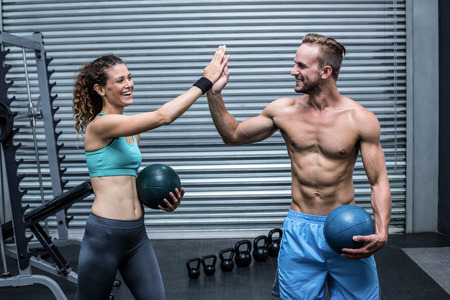 Muscular couple giving high five while holding exercise ball Stock Photo