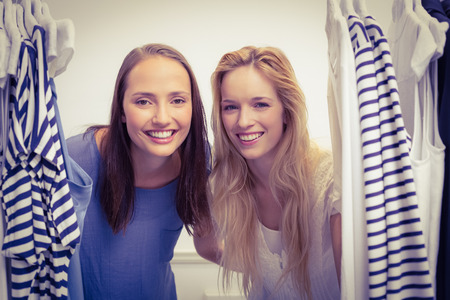 tienda de ropa: Retrato de dos amigos mirando a trav�s de la rejilla de ropa