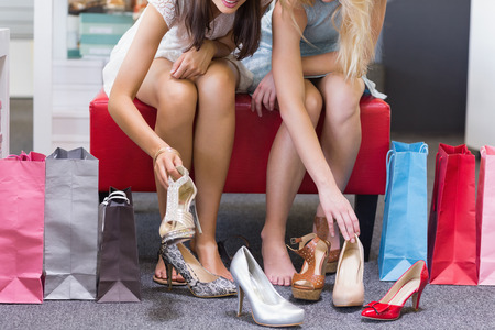 friends shopping: Close up of women trying on shoes in shoe shop