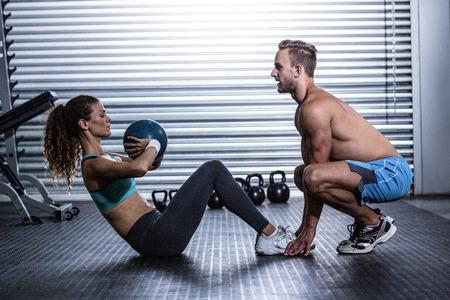 abdominal fitness: Vista lateral de una pareja muscular que hace ejercicio abdominal balón Foto de archivo