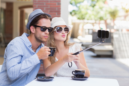 funny faces: Cute couple taking a selfie while doing funny faces
