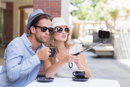 caras graciosas: Linda pareja tomando un selfie mientras hac�a muecas