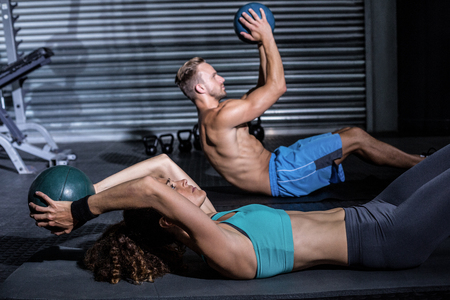 Muscular couple doing abdominal crunch with a ball