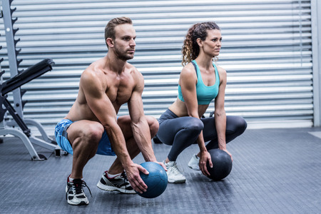 squatting: Squatting muscular couple doing ball exercise Stock Photo