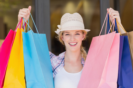 Portrait of an energetic woman handing shopping bags