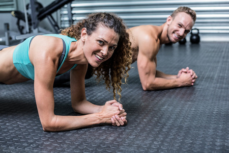 planking: Portrait of a muscular couple doing planking exercises