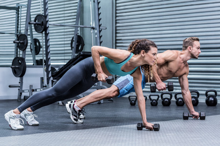 exercise room: Muscular couple doing plank exercise while lifting weights