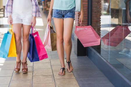 Close up of two women walking with shopping bags in shopping mall