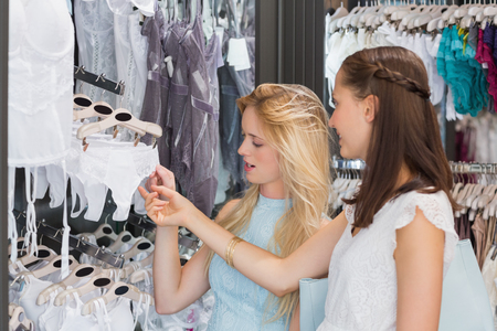 underwear: Happy women looking at underwear in shopping mall Stock Photo