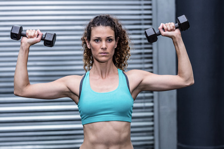A muscular woman lifting weights at the crossfit gym Stock Photo
