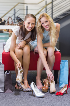 shoe shop: Two happy women smiling at camera and trying on shoes in shoe shop