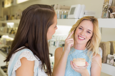 beauty shop: Happy blonde woman applying cosmetic products in a beauty salon