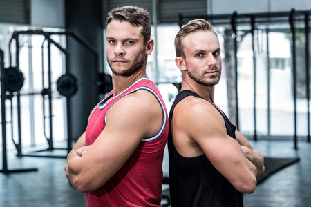 giving back: Portrait of two muscular men giving back to back Stock Photo