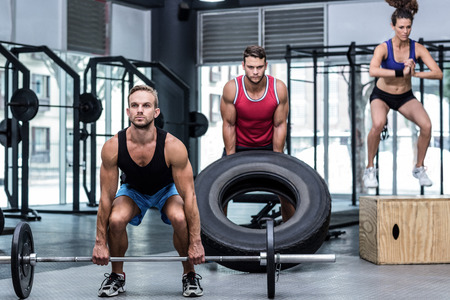 Three muscular athletes lifting and jumping at the crossfit gym