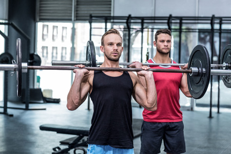 Muscular men lifting a barbell at the crossfit gym Stock Photo
