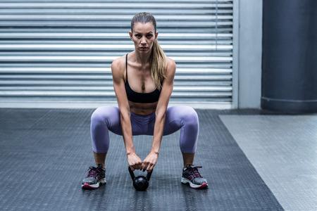 en cuclillas: Cuclillas musculares pesas elevaci�n de la mujer en el gimnasio CrossFit Foto de archivo