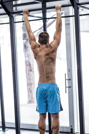 pull up: Vista posteriore di un uomo muscoloso che fa tirare su esercizi