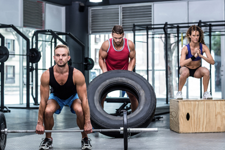 weight room: Serious three muscular people lifting and jumping in crossfit gym