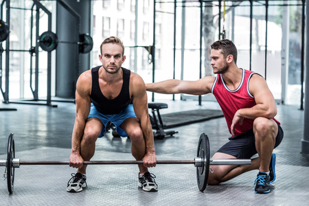 Trainer supervising a muscular man lifting a barbell Stock Photo