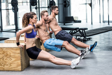 planking: Three muscular athletes doing planking at the crossfit gym