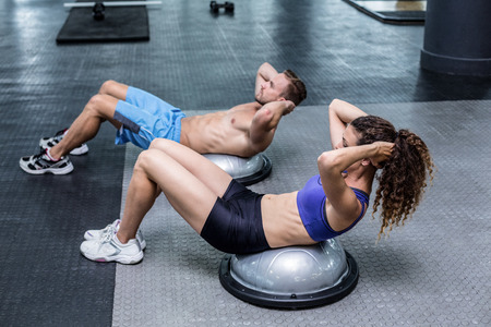 Muscular couple doing bosu ball exercises at the crossfit gym Stock Photo