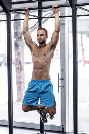 pull up: Front view of a muscular man doing pull up exercises