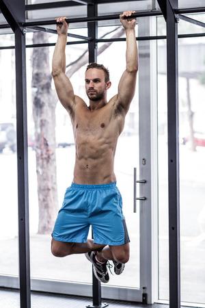 pull up: Vista frontale di un uomo muscoloso che fa tirare su esercizi Archivio Fotografico