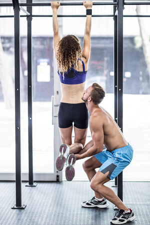 pull up: Trainer lifting a muscular woman doing pull up exercises