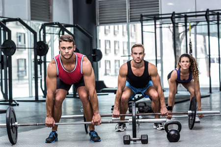 barbell: Portrait of a three muscular athletes lifting a barbell
