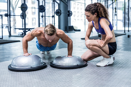 Trainer watching muscular man doing bosu ball push ups Stock Photo