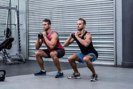 men exercising: Squatting muscular men exercising with kettlebells