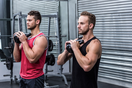 men exercising: Muscular men exercising with kettlebells at the crossfit gym Stock Photo