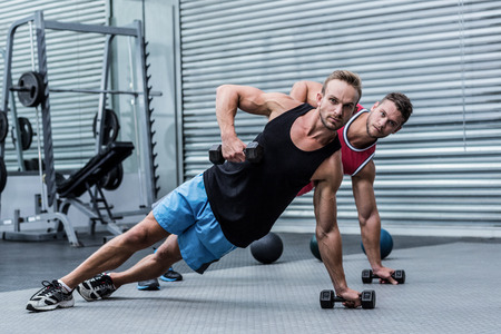 crossfit: Muscular men doing a side plank while lifting a dumbbell Stock Photo
