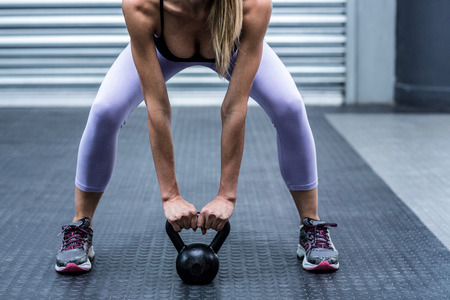 kettlebell: Squatting muscular woman lifting kettlebells at the crossfit gym